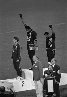 Extending gloved hands skyward in racial protest, U.S. athletes Tommie Smith, center, and John Carlos stare downward during the playing of the Star Spangled Banner after Smith received the gold and Carlos the bronze for the 200 meter run at the Summer Olympic Games in Mexico City on Oct. 16, 1968. Australian silver medalist Peter Norman is at left. (AP Photo)